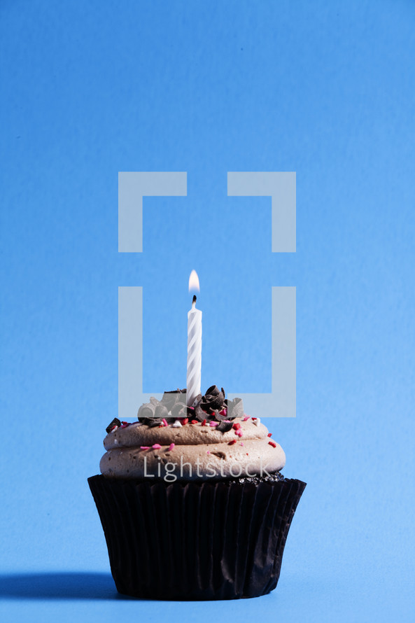 chocolate cupcake and candle on a blue background.