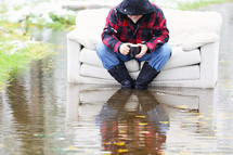 flood, man, sitting, couch, outdoors, water, coffee mug, wadding boots