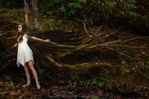 A fairy with wings spread near the roots of a tree.