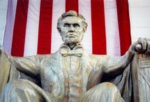 Abraham Lincoln Monument Statue with the US flag draped behind the statue.