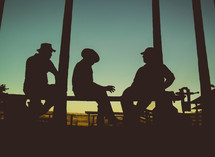 Silhouette of men sitting on rails at sunset.