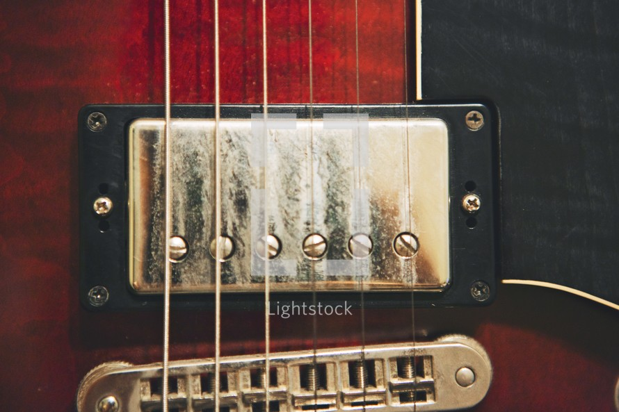 Close up of the bridge, saddle and strings of a guitar.