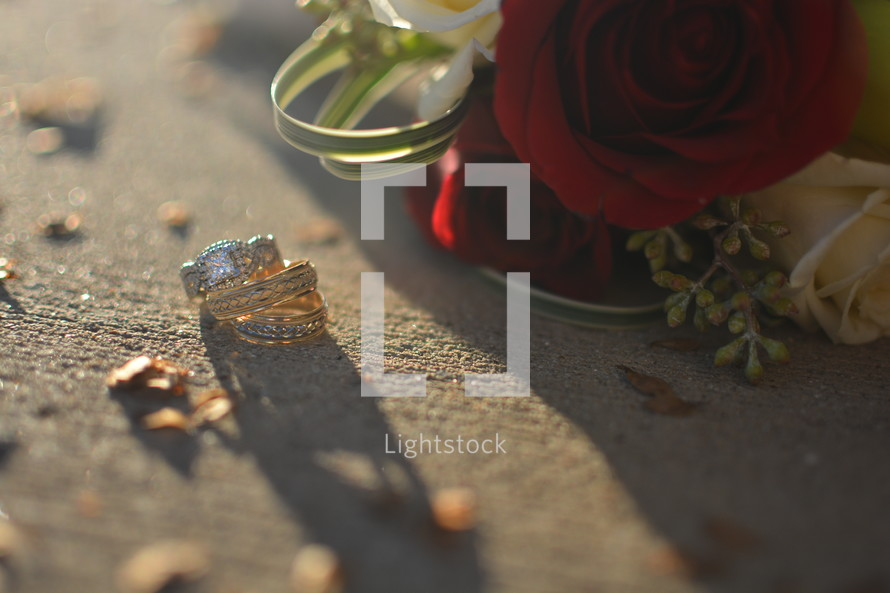 roses and wedding rings on a sidewalk