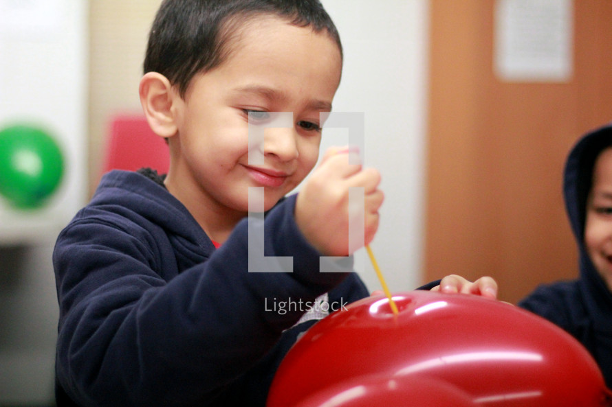Boy poking a balloon with a straw.