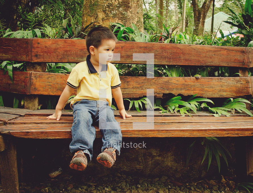a boy toddler looking worried while sitting on a bench