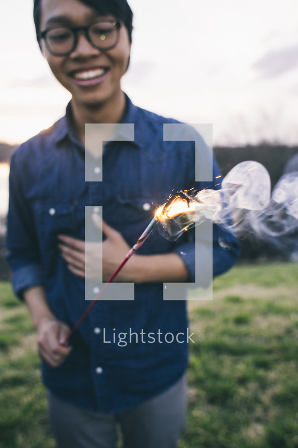 A young man holding a sparkler.