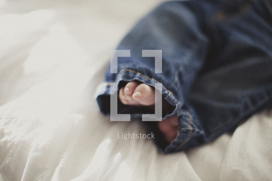 infant feet poking out of denim jeans