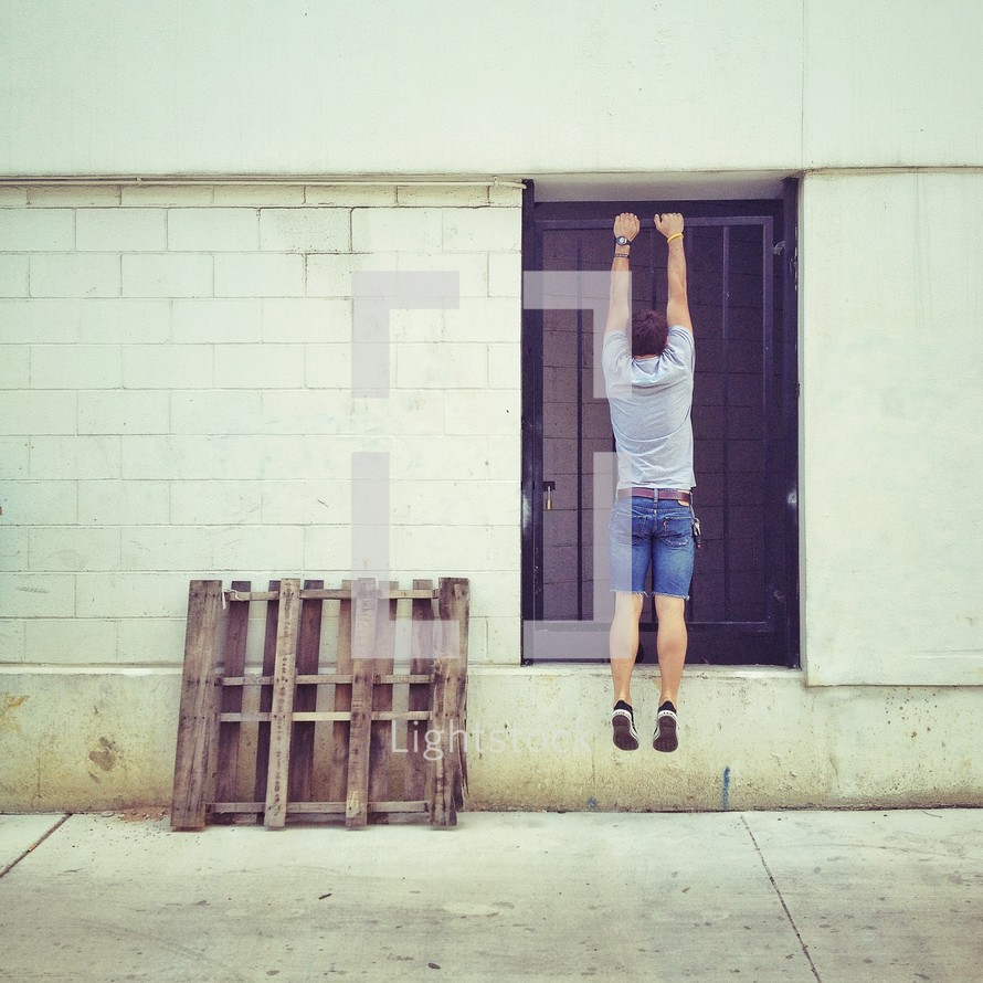 man hanging from a barred door