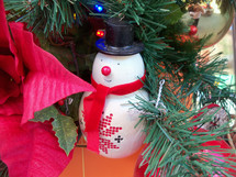 A snowman Christmas Tree ornament sits on the branch of a Christmas tree surrounded by red leaves and other beautiful Christmas ornament decorations in the celebration of Christmas time.  Frosty the Snowman was a favorite Christmas character we grew up with as kids and he has found a home here among familiar friends that adorn and decorate this Christmas tree to bring in the  Christmas holiday season.