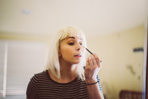 a woman putting on makeup