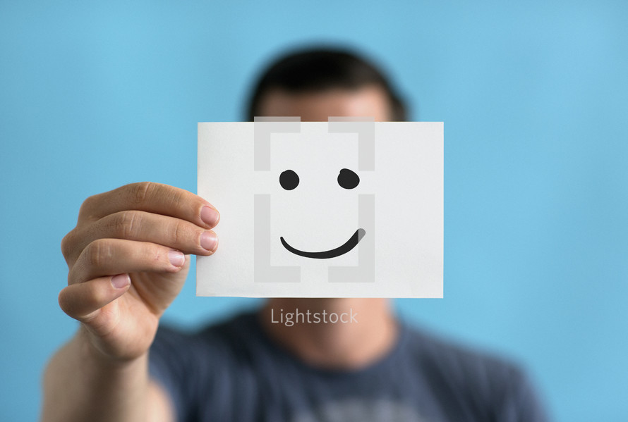 A man holding up a smiley face