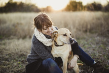 Smiling woman witting with her dog in a field.