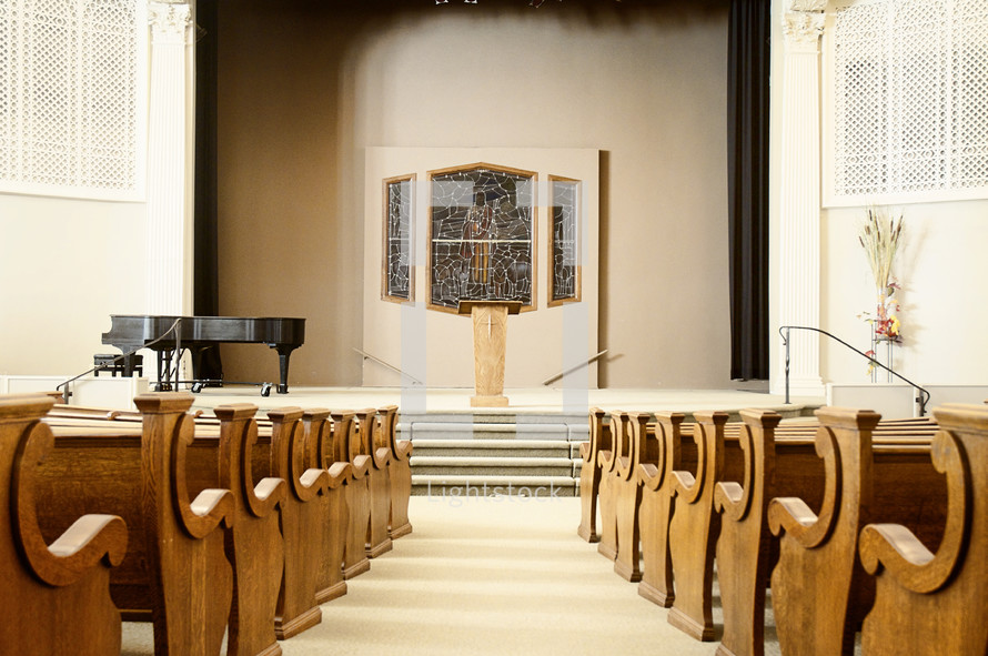 rows of pews and an altar in a empty church