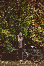 woman standing outdoors next to a bicycle