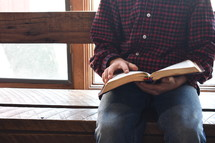 a man sitting in front of a window reading a Bible