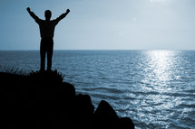 man with raised hands standing on a rock