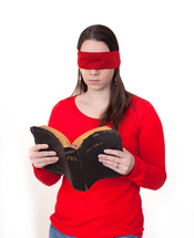 A blindfolded woman reading a Bible.