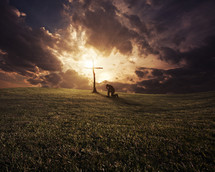 man kneeling in prayer in front of a cross under a cloudy sky
