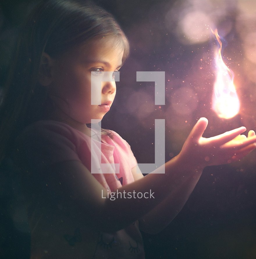 mesmerized child holding a flame