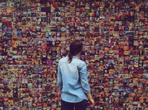 woman looking at a collage of photographs on a wall