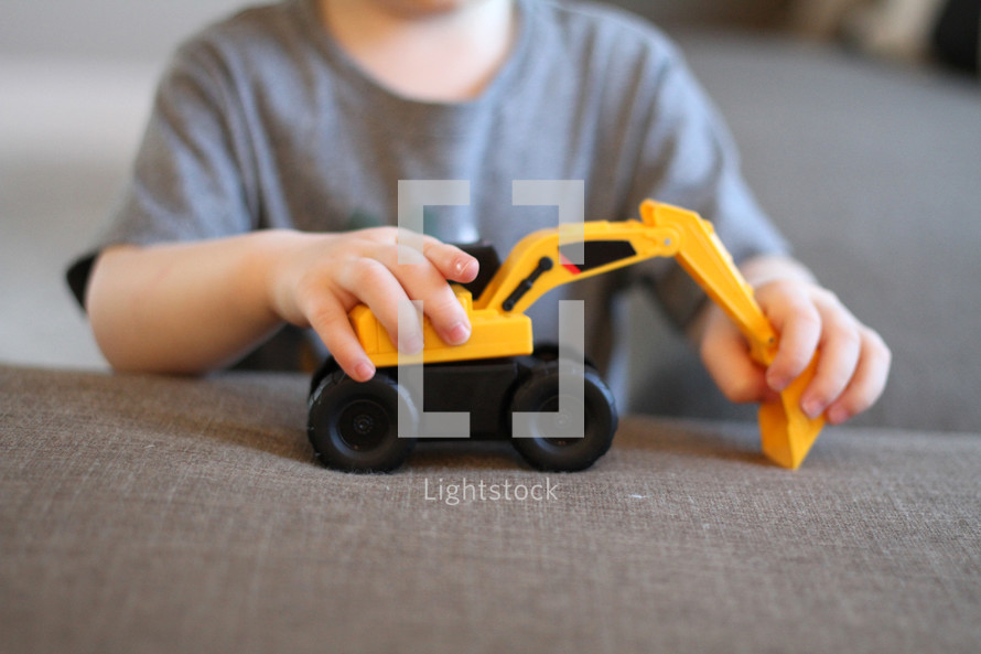 toddler boy playing with a toy excavator