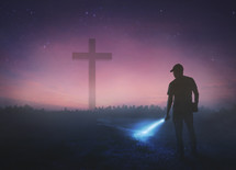 man holding a flashlight at night and a cross