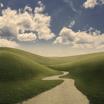 A pathway leading into the grassy field with rolling hills.