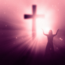 woman standing in front of a glowing cross with her hands raised in worship and praise