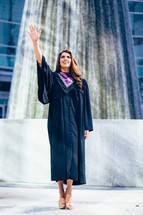 A woman in a graduation gown standing in front of a fountain with her arm raised.