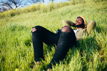 A man laying in a field of green grass.