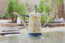 rain falling into a watering can