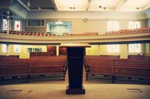 rows of church pews, podium, altar, empty church