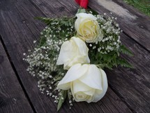 A bouquet of white roses surrounded by babies breathe draped over an old wooden bench for a special wedding day, valentines day or any celebration of love between  a man and a woman.