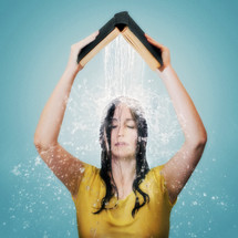 A woman holding an open Bible above her head as water pours on her.