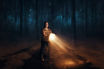 a woman in the woods at night using a Bible as her flashlight