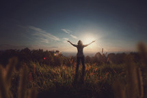 woman in a field with her arms held out in worship to God
