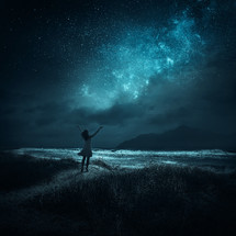 A woman stands with her arms raised toward the Milky Way.