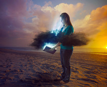 rays of light coming through the clouds as a woman opens a Bible