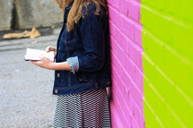 a teen girl reading a Bible in front of a colorful painted brick wall