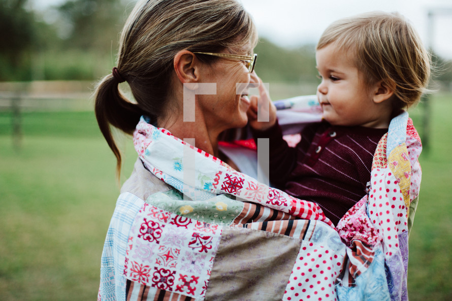 grandmother holding her grandson wrapped in a blanket