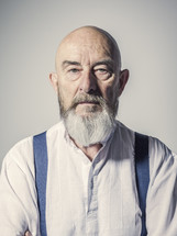 a bald man with a beard in suspenders