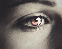Closeup of an eye looking an at illuminated cross.