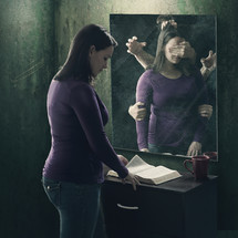 a woman seeing demons in a mirror