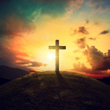 a cross on a hill at sunrise