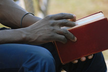 man resting holding a Bible