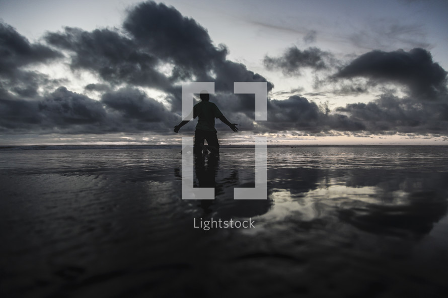 a man kneeling on a beach on wet sand at sunset