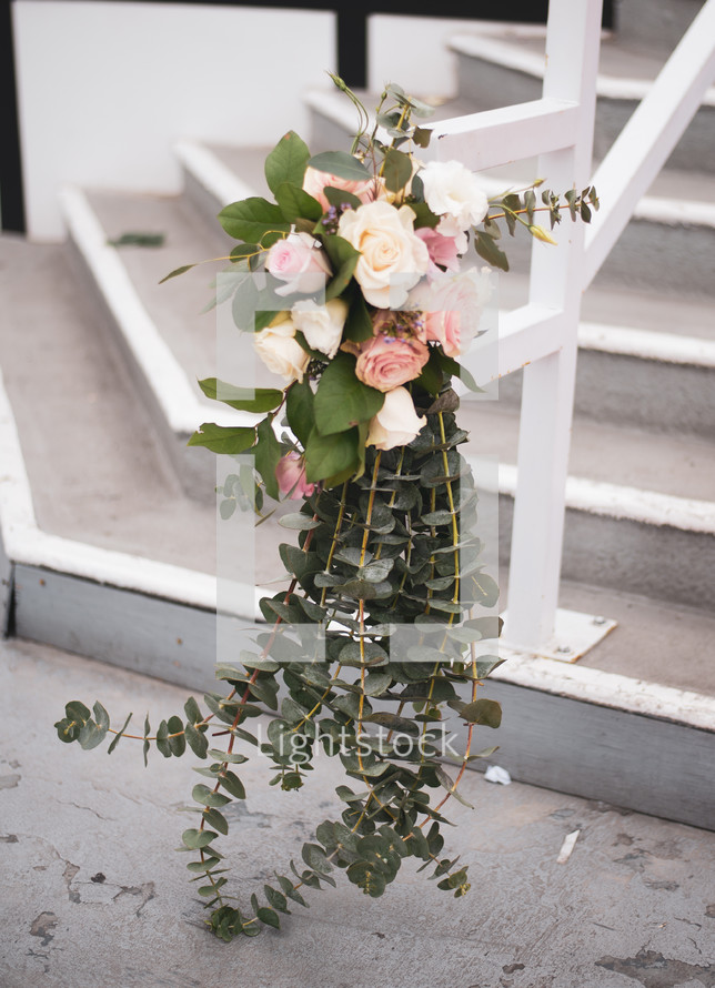roses and eucalyptus on a railing