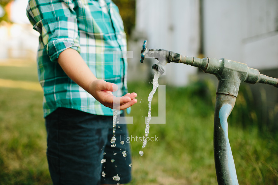 Boy reaching under water spicket