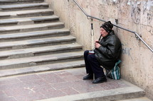 A blind man playing a recorder on stone steps for money