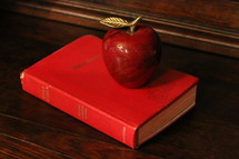 apple paper weight on a Bible